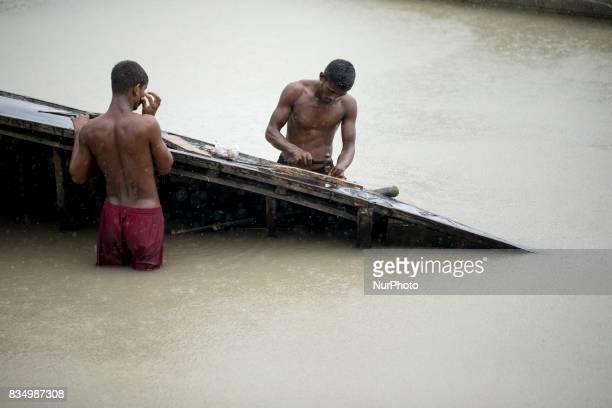 Boat men repair their boat at Shariakandi Bogra Bangladesh 17 August 2017 According to authorities floods caused by heavy rainfall lashing Bangladesh...