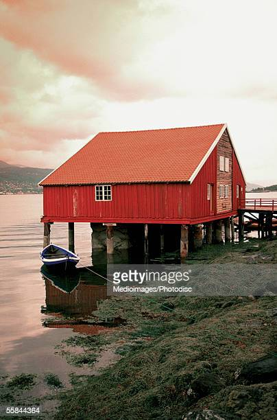 Boat moored near a red house at the beach, Bergen, Norway