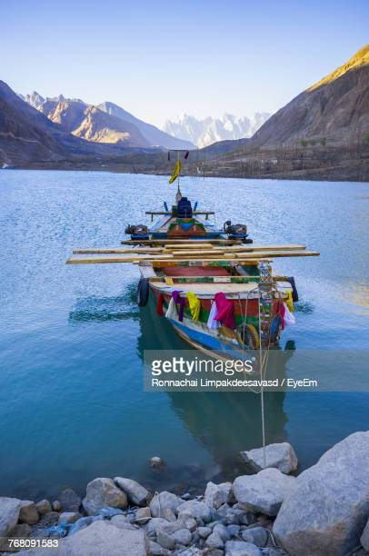 Boat Moored On Lake By Mountains Against Clear Sky