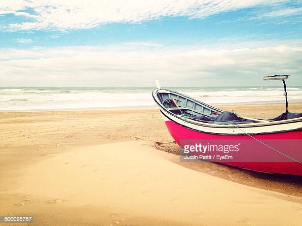Boat moored on shore with sea below clouds at distance