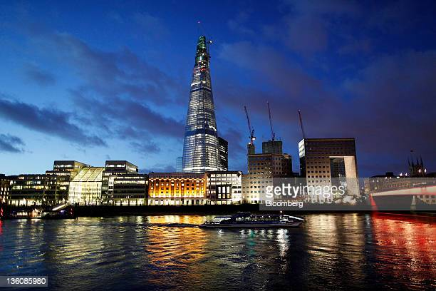 A boat moves along the River Thames against the backdrop of the Shard tower in London UK on Tuesday Dec 13 2011 City of London office projects this...