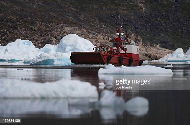 A boat navigates among calved icebergs from the nearby Twin Glaciers on July 31 2013 in Qaqortoq Greenland Boats are a crucial mode of transportation...