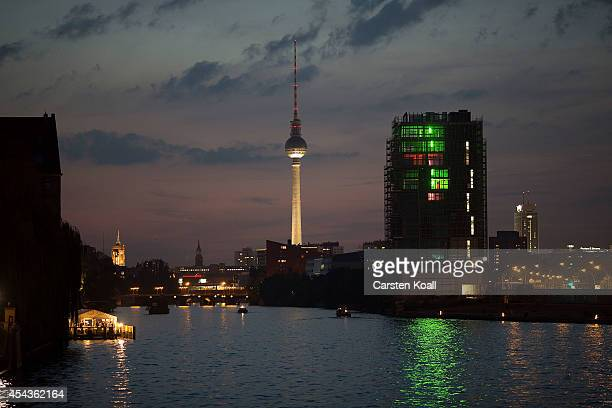 A boat navigates the Spree River at twilight in the city center as a newlybuilt apartment building and the illuminated broadcast tower at...