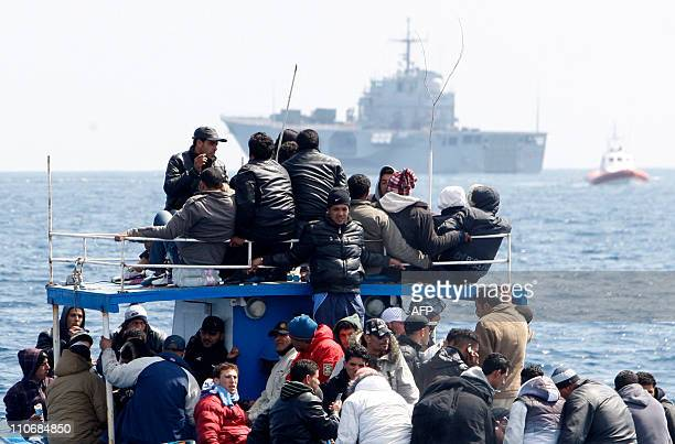 A boat of wouldbe immigrants passes by the San Marco an Italian Navy ship waiting to evacuate some 700 immigrants on March 23 2011 off the Italian...