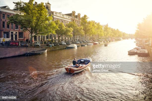 Boat on a canal in Amsterdam at sunset, Netherlands
