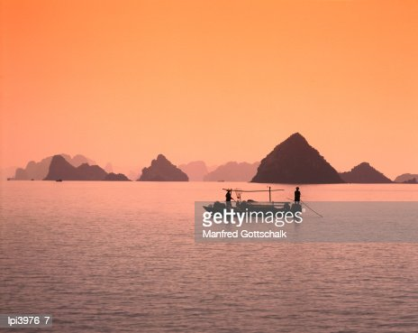Boat on bay waters with islets in background, Halong Bay, Vietnam : Stock Photo