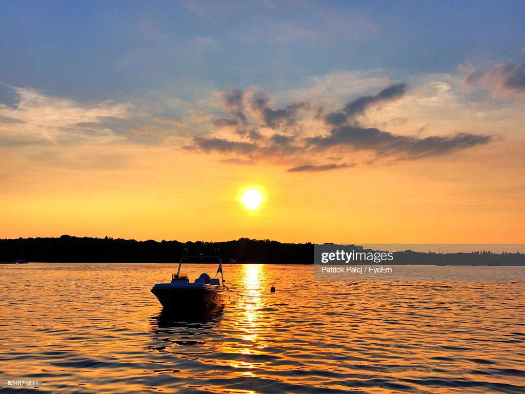 Boat On Lake Against Sky During Sunset
