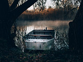 Boat on misty lake. Old fishing boat.