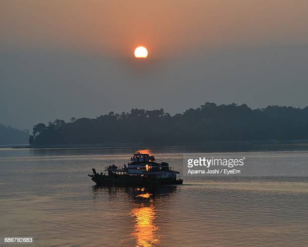 Boat On River Against Sky During Sunrise