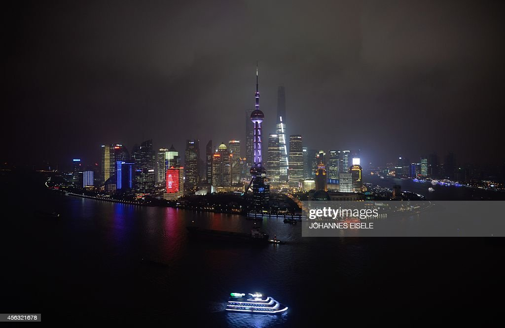 A boat on the Huangpu River passes the skyline of the Lujiazui Financial District in Pudong in smog in Shanghai on September 29 2014 China hailed the...