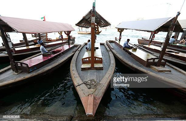 Boat operators wait for customers for their abra water taxi services on a waterway in Al Ghubaiba's creek district of Dubai United Arab Emirates on...