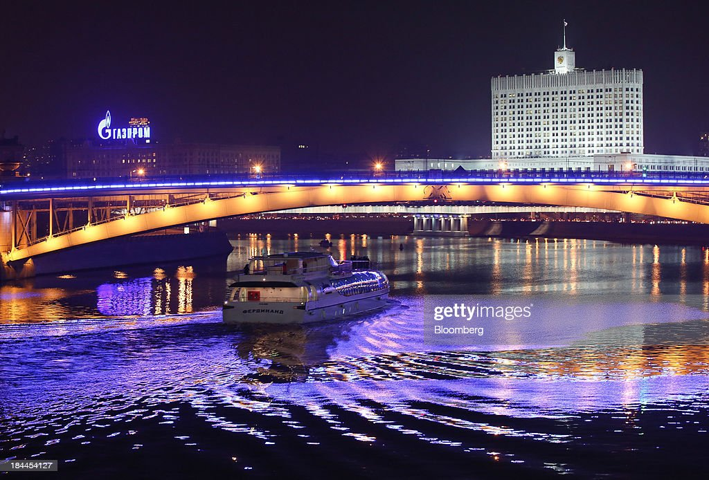 A boat pass beneath a bridge on the River Moskva beyond the Russian White House, right, and an illuminated OAO Gazprom advertisement in Moscow, Russia, on Thursday, Oct. 10, 2013. Tinkoff Credit Systems Bank, operated by TCS Group Holding Plc, is valued at $2.5b to $3b for London IPO, which reflects P/E multiple of 9.5 to 11.4, Vedomosti reports, citing unidentified people familiar with offering documents. Photographer: Andrey Rudakov/Bloomberg via Getty Images