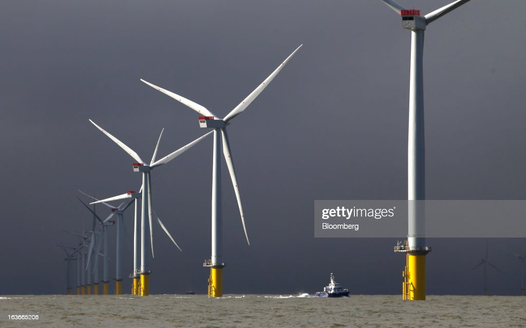 A boat passes between wind turbines at the London Array project, the world's largest consented wind farm, a partnership between Dong Energy A/S, E.ON AG and Abu Dhabi-based Masdar in the Thames Estuary, U.K., on Wednesday, March 13, 2013. 'London Array will soon be the largest operational offshore wind farm in the world,' said Benj Sykes, head of Dong Energy's U.K. wind business. Photographer: Chris Ratcliffe/Bloomberg via Getty Images