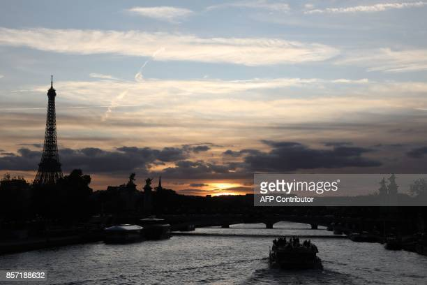 A boat passes on the River Seine near the Eiffel Tower at sunset in Paris on October 3 2017 / AFP PHOTO / LUDOVIC MARIN