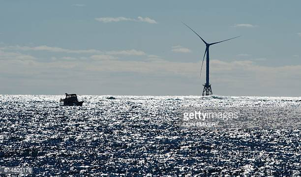 A boat passes one of the wind turbines of the Block Island Wind Farm on October 14 2016 off the shores of Block Island Rhode Island The first...