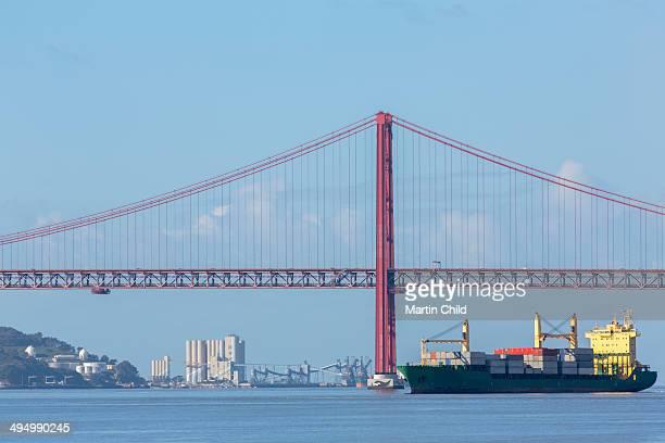 Boat passing Ponte 25 de Abril bridge, Lisbon
