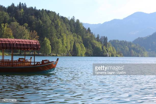 Boat Sailing On Lake By Trees Against Sky
