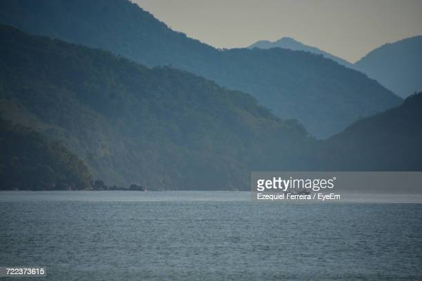 Boat Sailing On Sea Against Mountains