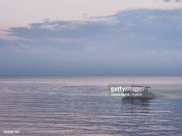 Boat Sailing On Sea Against Sky