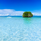 Small white sailboat sailing next to remote tropical island in lagoon.Transparent clear blue water with isolated island green in background.