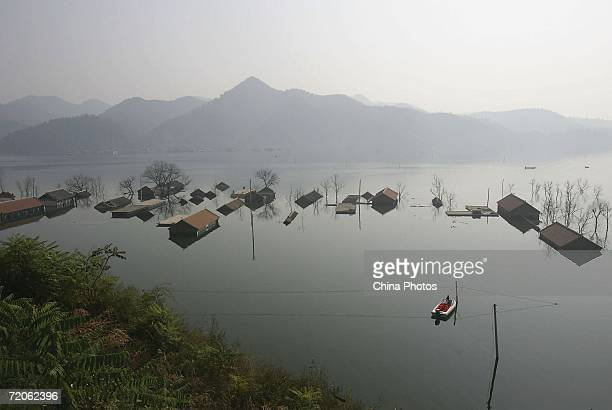 A boat sails beside the roofs of submerged houses at the Huanxiu Lake on October 1 2006 in Jixian County of Tianjin Municipality China A village was...
