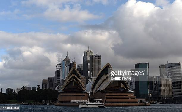 A boat sails in front of the Sydney's Opera House in Sydney on May 22 2015 Earlier a severe weather warning was issued for Sydney and adjoining areas...