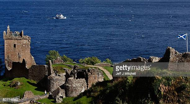 A boat sails on Loch Ness as a Saltaire flies over Urquhart Castle which has been voted Britain's favourite tourist spot September 11 2008 in...
