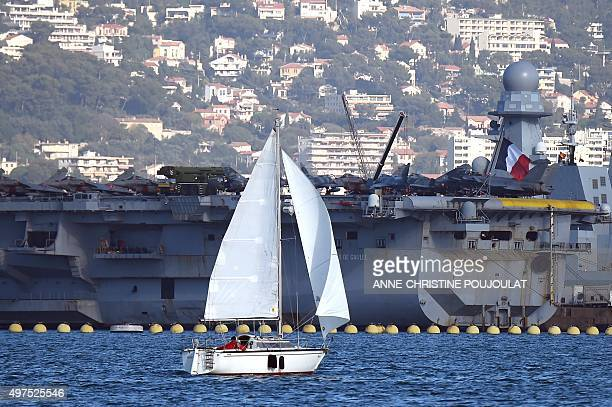 A boat sails past the Charles de Gaulle the flagship of the French Navy and the largest western European warship currently in commission is seen...