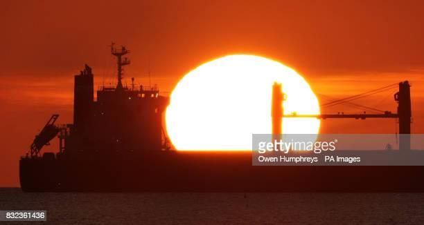 A boat sails past the rising sun at King Edwards Bay Tynemouth