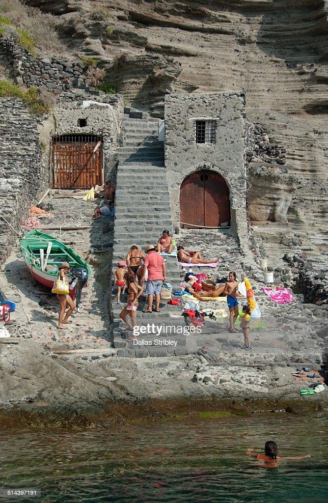 Boat sheds and people at Pollara, Salina, Italy