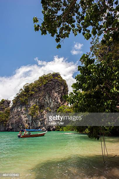 A boat sits off a secluded beach at Kilim Karst Geoforest Park on Langkawi an island in north West Malaysia Formed more than half a billion years ago...