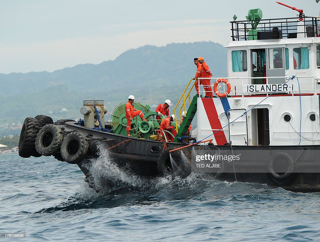 A boat sprays chemical despersal to contain an oil spill believed to be from a sunken ferry in Talisay town near Cebu City, central Philippines on August 18, 2013, two days after a ferry and a freighter collided. Philippine rescuers struggled in rough seas August 18, as they resumed a bleak search for 85 people missing in the country's latest ferry disaster, but insisted miracle survivor stories were possible.