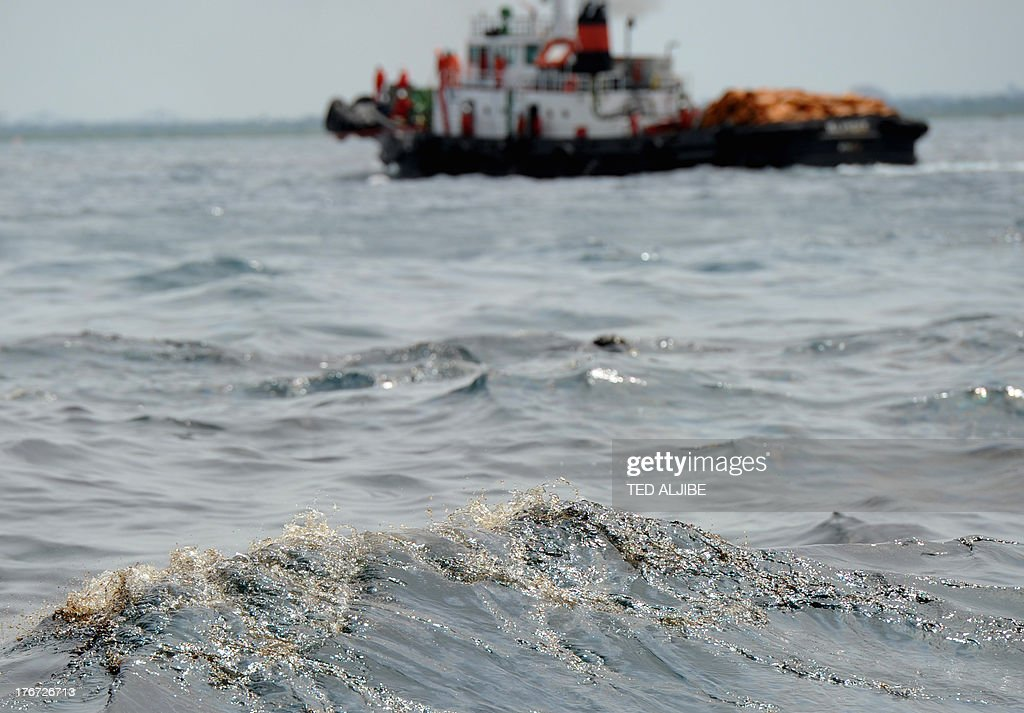 A boat sprays chemical despersal to contain an oil spill (foreground) believed to be from a sunken ferry in Talisay town near Cebu City, central Philippines on August 18, 2013, two days after a ferry and a freighter collided. Philippine rescuers struggled in rough seas August 18, as they resumed a bleak search for 85 people missing in the country's latest ferry disaster, but insisted miracle survivor stories were possible.