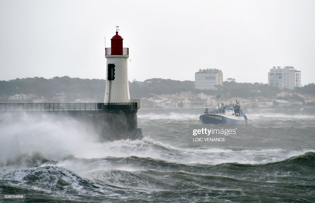 A boat steers near a lighthouse as a wave breaks at a pier in Les Sables-d'Olonne, western France, on February 9, 2016. High winds buffeted northwestern Europe on February 8, leaving one woman in France in a coma after she was hit by an advertising hoarding. Electricity was cut to 5,000 homes in northern France. / AFP / LOIC VENANCE
