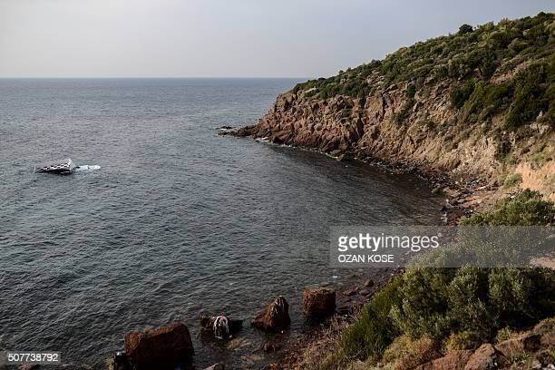 A boat that capsized is seen near the coast on January 31 2016 in Canakkale's Bademli district after at least 37 migrants drowned when their boat...