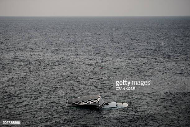 A boat that capsized is seen on January 31 2016 in Canakkale's Bademli district after at least 37 migrants drowned when their boat sank in the Aegean...