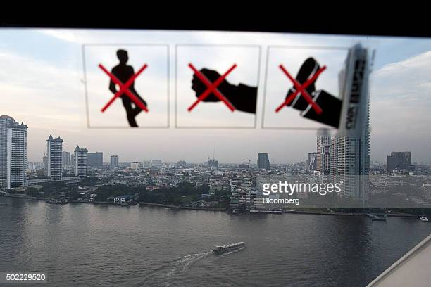 A boat traveling along the Chao Phraya river is seen through the window of a passenger pod on the ferris wheel at Asiatique The Riverfront openair...