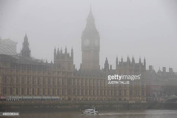 A boat travels along the River Thames through the fog past the Houses of Parliament in central London on November 2 2015 Thick fog across much of...