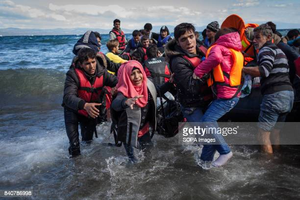 A boat with refugees arrives on the Greek shores near Skala Skamineas on the Greek island of Lesbos The mountains at the back are the Turkish coasts...