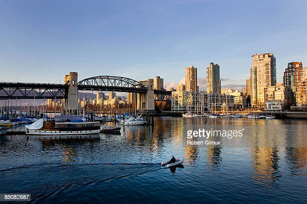 A boater motors towards the Burrard street bridge as the sun sets on the city skyline February 18 2009 in Vancouver British Columbia Canada Vancouver...