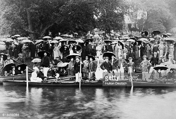 Boaters in punts and along shore posing for group portrait | Location Cambridge England UK