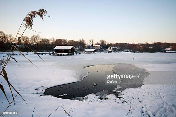 Boathouses at the frozen Lake Chiemsee in winter, Bavaria, Germany