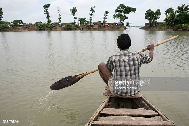Boatman Bhikhan Mukhiya paddles towards a road embankment which was breached by rising floodwaters near the village of Dekha Batraulia in east...