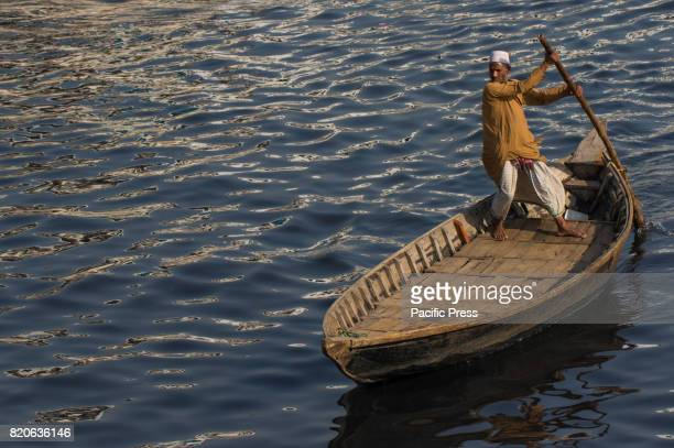 SADARGHAT DHAKA BANGLADESH A boatman is ready to carry workers from the outskirts to their jobs in the centre of the city The view of Sadarghat area...