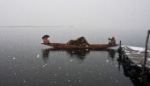 A boatman rows his boat amid the snow fall in Dal lake on Jannuary 10 2014 in Srinagar the summer capital of Indian administered Kashmir India...