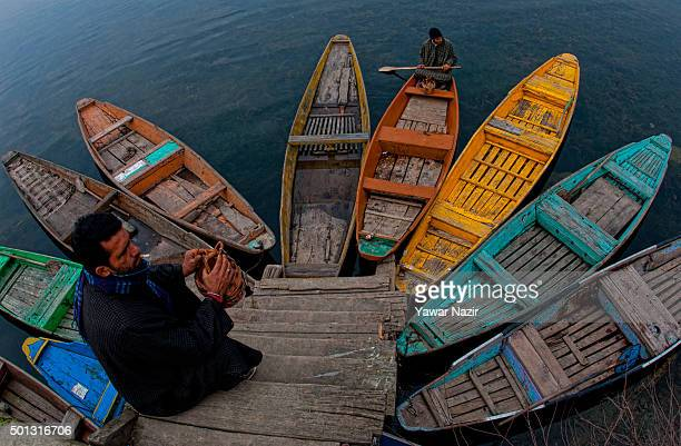 A boatman rows his boat oas a man sits on a dock n the Dal Lake on December 14 2015 in Srinagar the summer capital of Indian administered Kashmir...