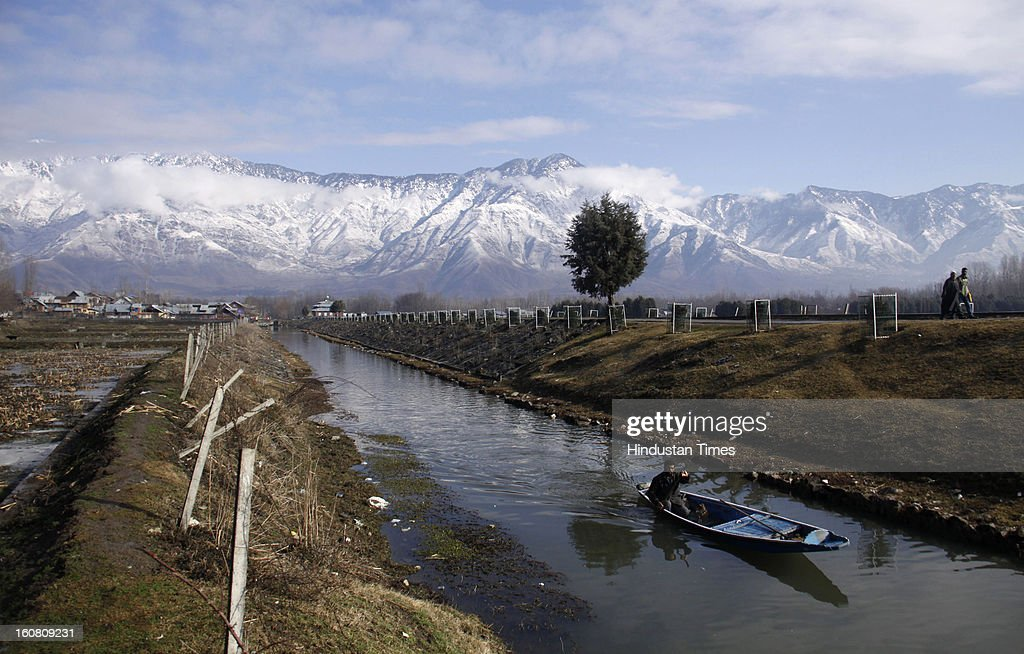 A boatman rows his boat through a canal during a sunny day, on February 6, 2013 in Srinagar, India. After two days of intermittent snow and rain weather improved in Kashmir. .