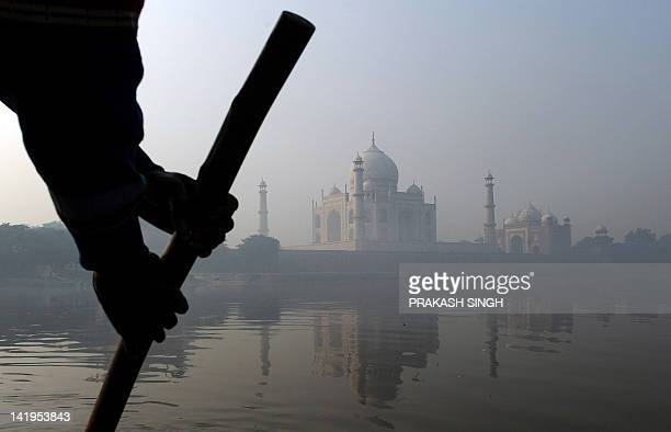 A boatman rows in the Yamuna river against the backdrop of the landmark Taj Mahal in Agra on December 5 2010 French President Nicolas Sarkozy is on a...