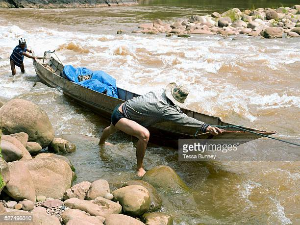 Boatman So and his son Somvang push their boat through shallow rapids on the Nam Ou river during the dry season when the river level is low Phongsaly...