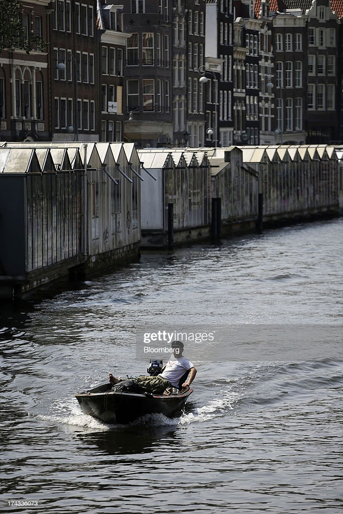 A boatman steers his vessel along a canal past residential buildings in Amsterdam, Netherlands, on Tuesday, July 23, 2013. Dutch pension funds will be allowed to calculate liabilities on the basis of an adjusted discount rate as the government seeks to keep the retirement system viable amid low interest rates and an aging population. Photographer: Matthew Lloyd/Bloomberg via Getty Images